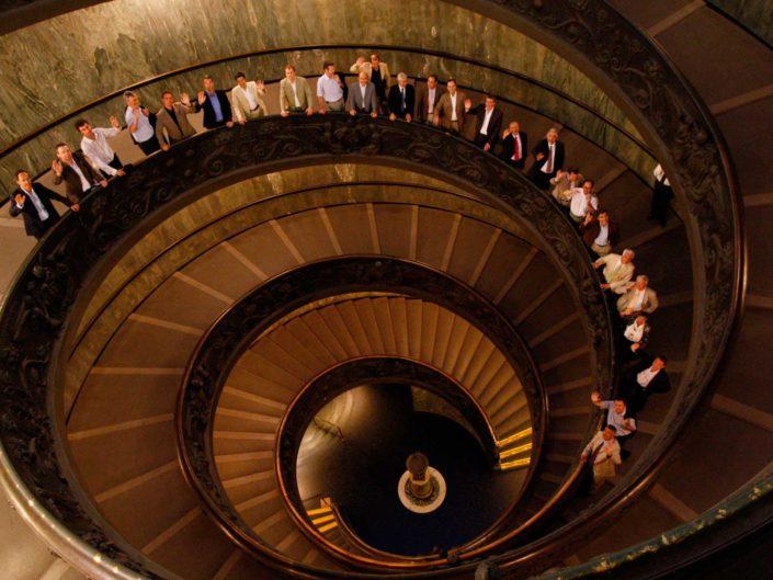 Foto di gruppo aziendale sulla scala elicoidale dei musei Vaticani, durante una visita privata.