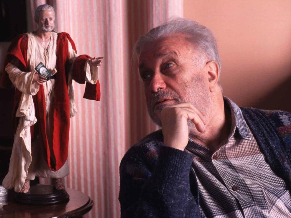 Lo scrittore Luciano De Crescenzo nella sua casa romana accanto alla statuetta del Presepe a lui dedicata dagli artisti napoletani. Novembre 2000
