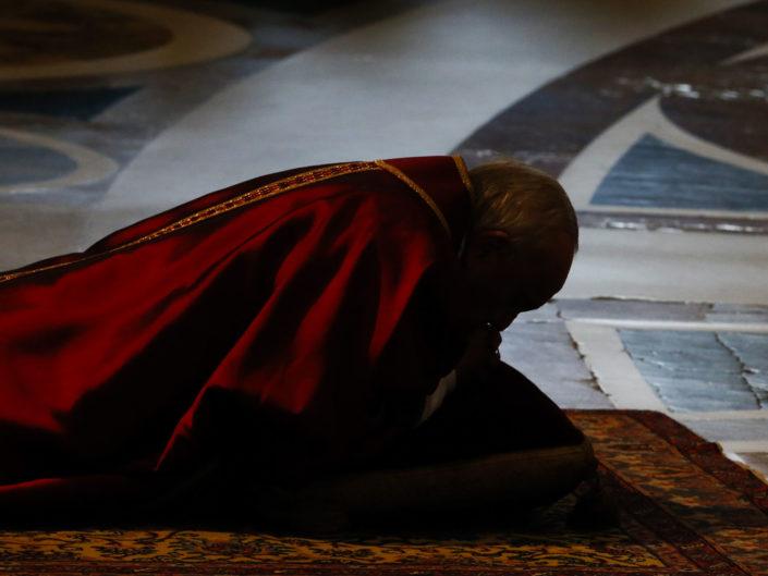 Papa Francesco prega sul pavimento della Basilica di San Pietro durante la celebrazione della passione di Cristo. Roma 14 Aprile 14 2017