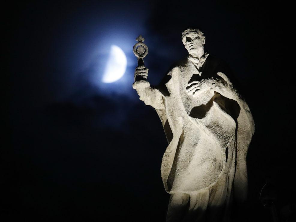 La luna risplende alle spalle di una statua in Piazza San Pietro, 5 ottobre 2019