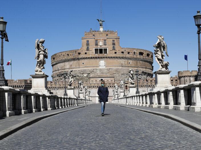 Una donna con mascherina protettiva attraversa Ponte Sant'Angelo deserto a causa del Coronavirus (Covid-19), Roma 23 marzo 2020